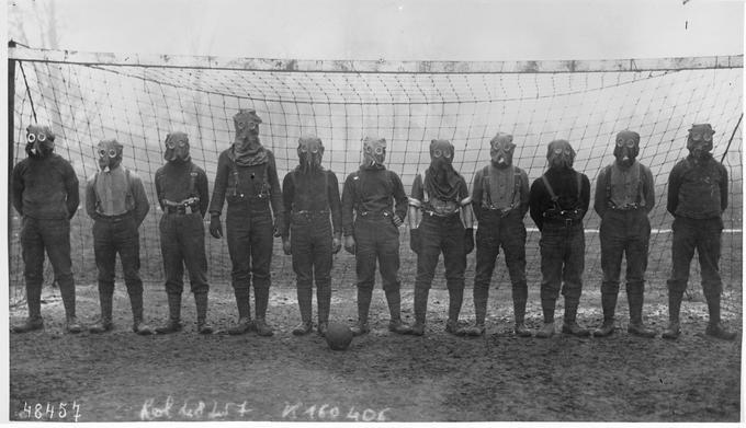 Bildet viser et fotballag som består av britiske soldater et sted i Frankrike under 1. verdenskrig. Alle har gassmasker på.