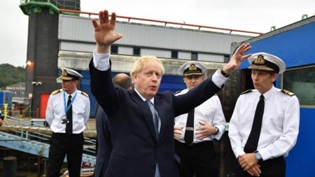 Bildet viser Storbtiannias statsminister Boris Johnson i halvfigur som gestikulerer med hendene i været. I bakgrunnen fire menn i marineuniformer.
