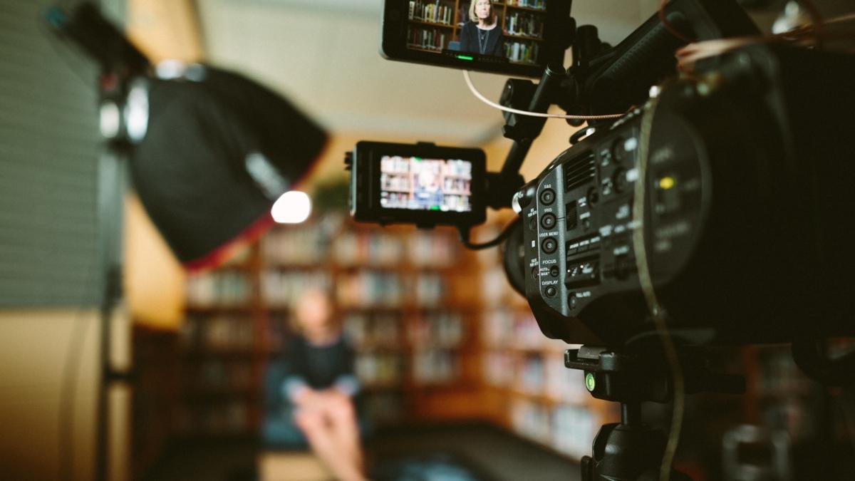 Bildet viser filmopptak av en kvinne som sitter foran en bokhylle