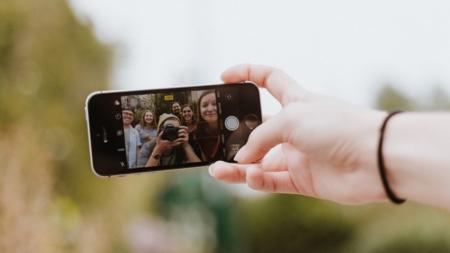 Bildet viser en hånd som holder en smarttelfon. Smarttelefonens skjerm viser en glad vennegjeng.