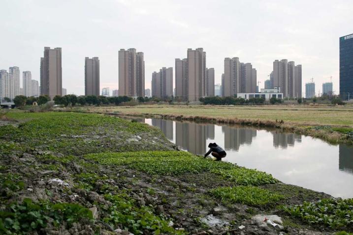 Bilde som kontrasterer megaby i bakgrunnen mot bonde som luker i forgrunnen