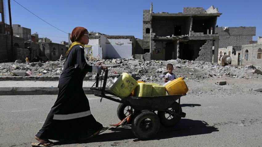 Kvinne frakter vann i ruiner i Sana.