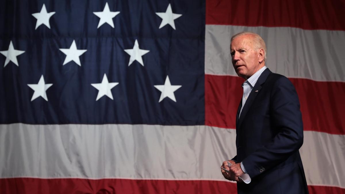 Bildet viser Joe Biden i halvfigur foran et stort amerikansk flagg