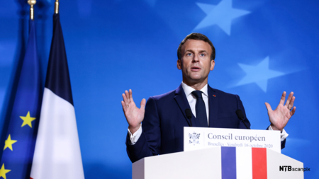 Bildet viser Frankrikes president Emmanuel Macron på talerstolen. Han slår ut med hendene og er i halvfigur.