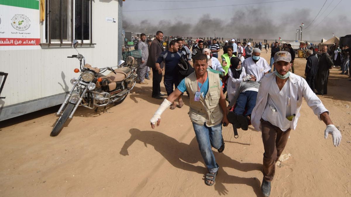 Bildet viser palestinere som evakuerer en såret mann under protester på Gazastripen våren 2018