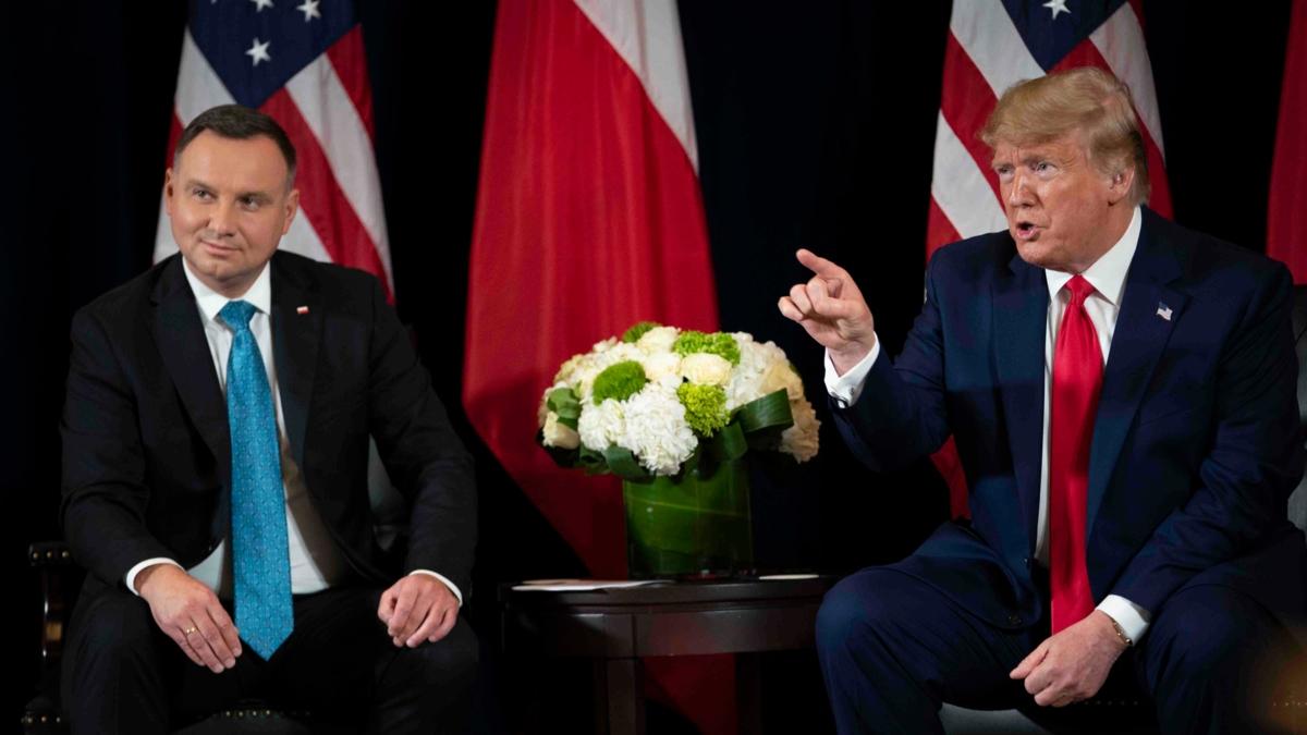Bildet viser Polens president Andrzej Duda og Donald Trump sittende på en scene foran sine respektive lands flagg i USA i september 2019.