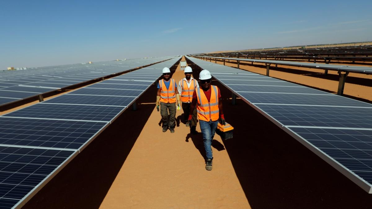 Bildet viser tre arbeidere som går mellom solcellepanelene på solkraftstasjonen Benban i Aswan, Egypt.