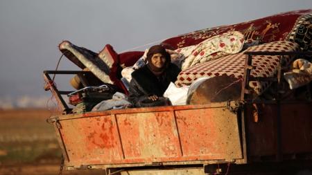 På bildet flykter en syrisk kvinne med eiendelene sine på et lasteplan etter sammenstøt i al-Bab 7. januar.