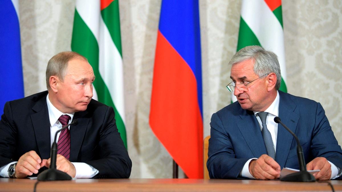 Bildet viser Russlands president Vladimir Putin og tidligere leder for Abkhazia, Raul Khadzhimba, i samtale foran sine respektive flagg i 2017