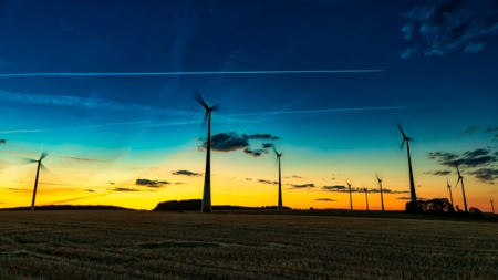 The image shows windmills at sundown